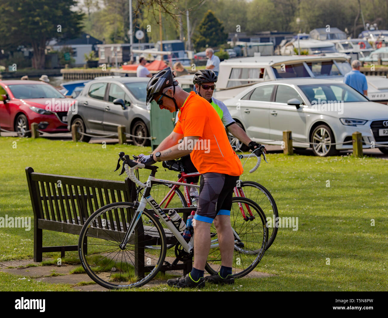Two male cyclists getting their road bicycles ready to carry on their journey after spending a few minutes resting on a wooden bench in a public park  Stock Photo