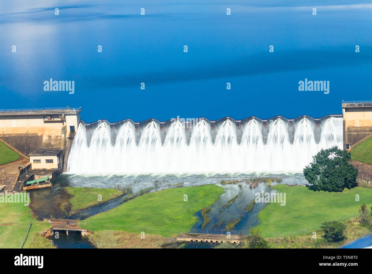 Full dam waters overflowing wall structure closeup flying air photo overlooking natures power. - Stock Image