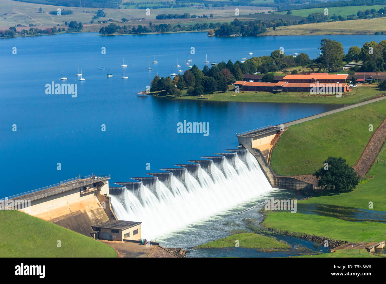 Flying air photo of dam wall overflowing waters moored boats scenic countryside landscape. - Stock Image