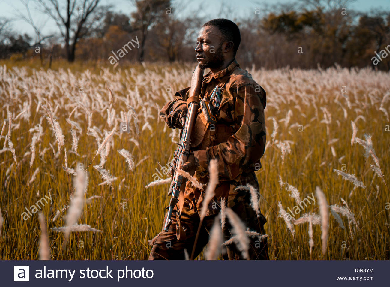 Anti poaching ranger patrolling in the central african grasslands. - Stock Image
