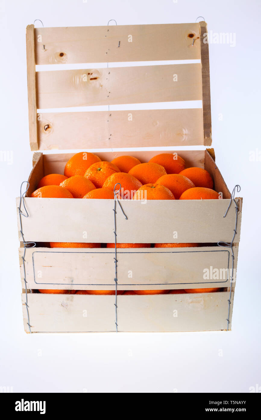 Oranges in large wooden box - isolated on a white background - Stock Image