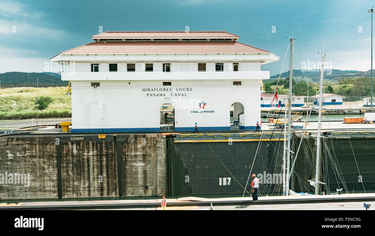 Canal employees guide by hand three sailboats rafted together through the Miraflores Lock using lines - Stock Image