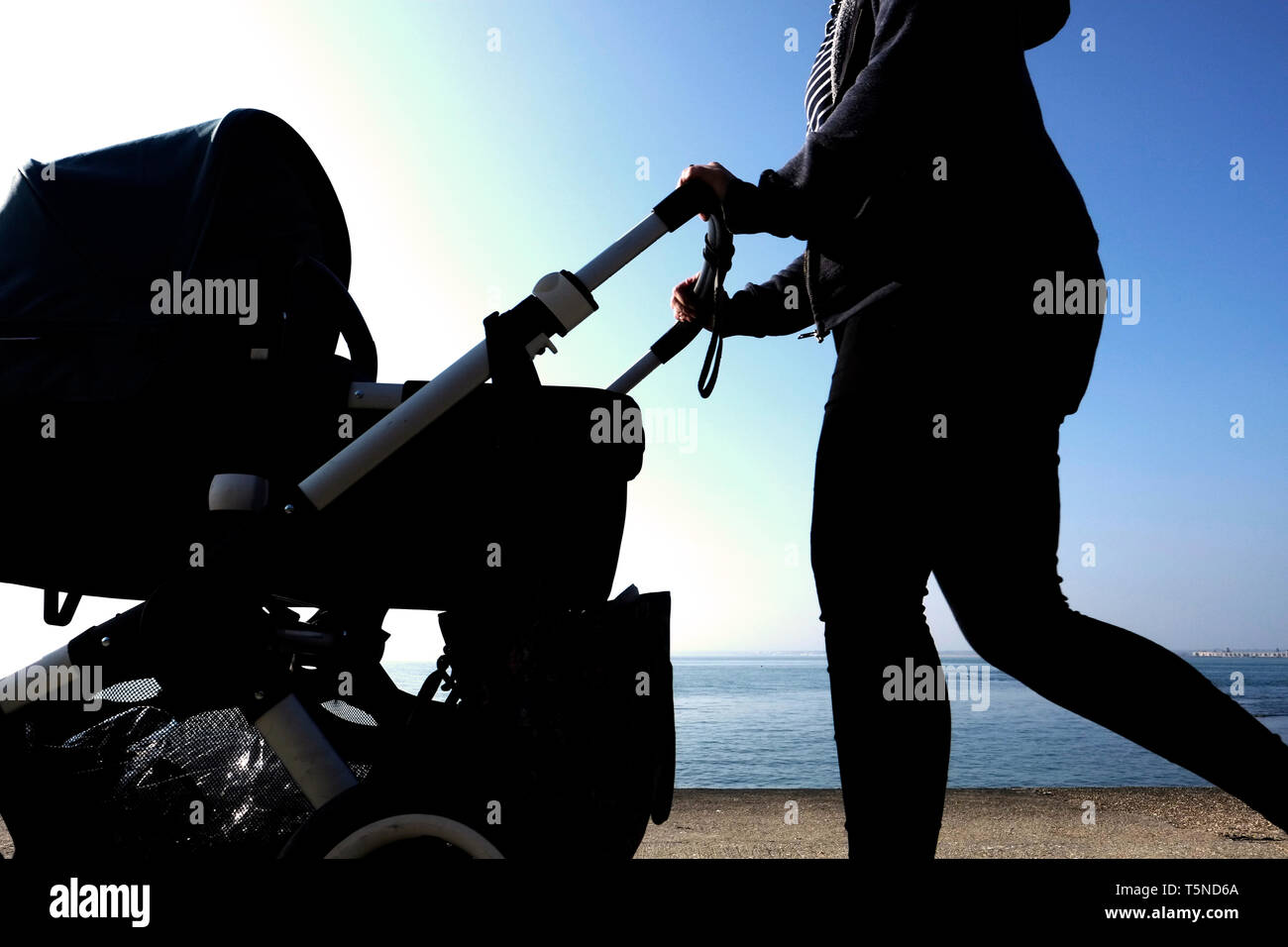 A woman pushing a pram or buggy out for a walk by the seaside partly in silhouette with the sea horizon and blue sky in the background. - Stock Image
