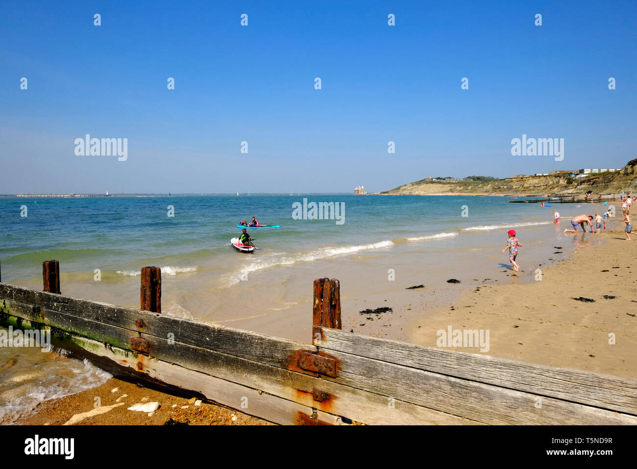Colwell Bay during the Easter weekend 2019 heatwave and the beach is full of people sunbathing and taking part in all manner of seaside activity. - Stock Image