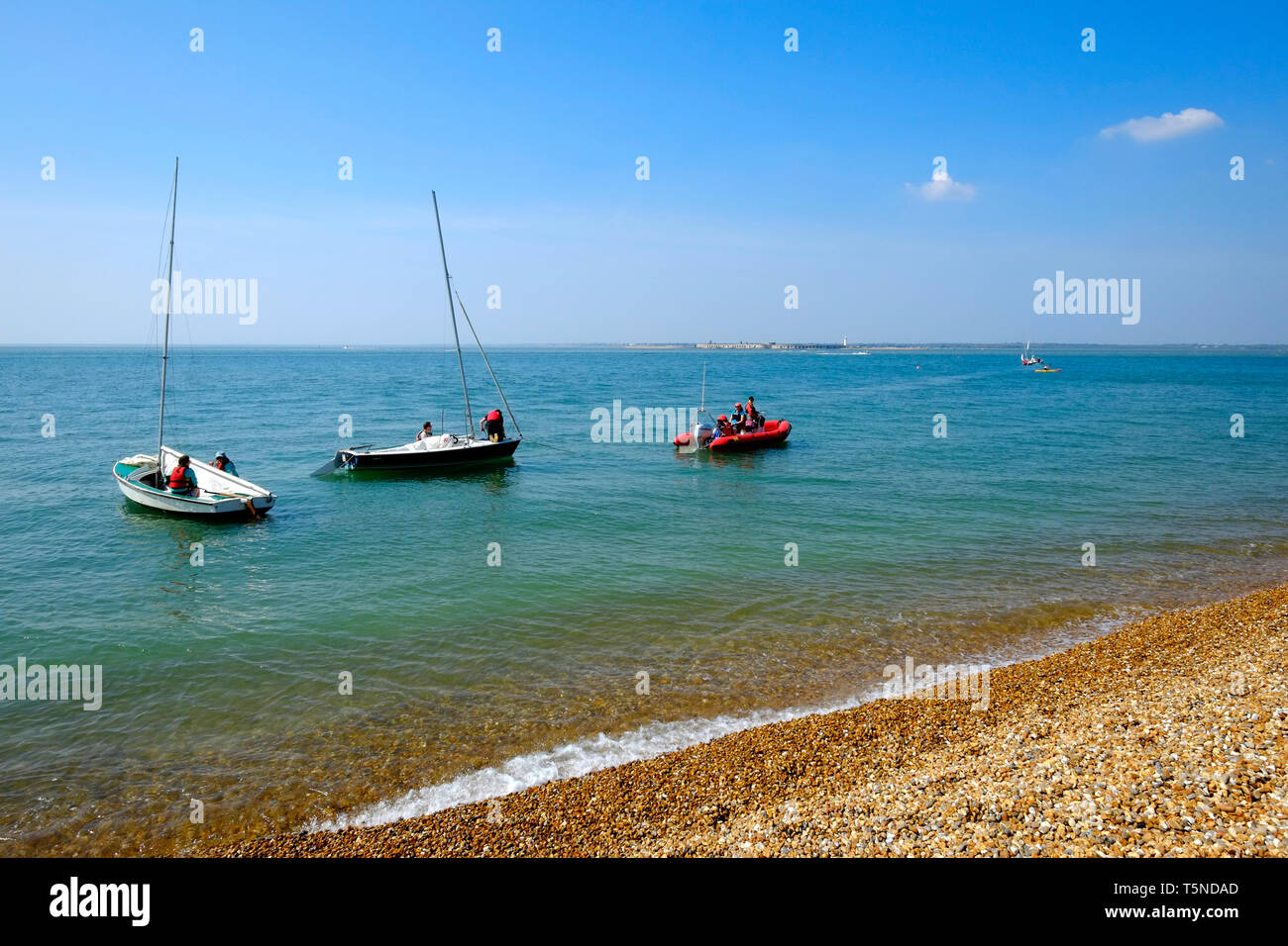 Small sailing boats anchored just off the beach at Colwell Bay in beautifully sunny weather, Isle of Wight, UK. - Stock Image