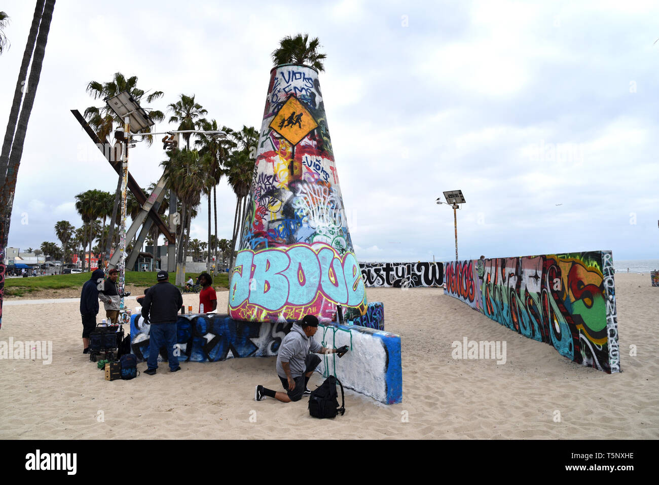 LOS ANGELES, CA/USA  - APRIL 19, 2019:  Taggers painting the famous Venice Beach graffiti walls on a hazy day - Stock Image