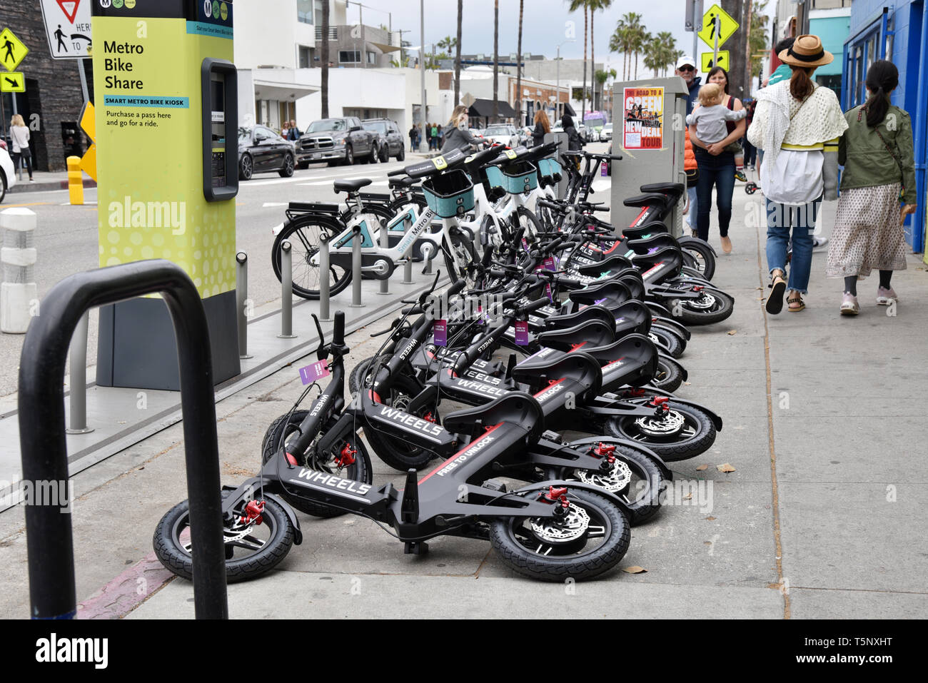LOS ANGELES, CA/USA  - APRIL 19, 2019:  Electric rental bikes and e-scooters clog the streets and sidewalks on Abbot Kinney Blvd in Venice Beach - Stock Image