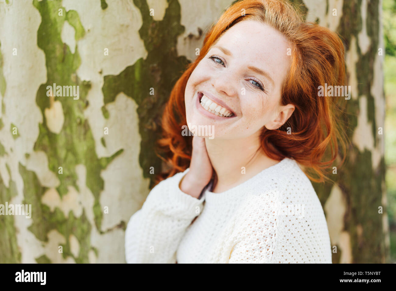 Smiling happy young redhead woman with a toothy grin standing in front of a large tree trunk turning to smile at the camera - Stock Image