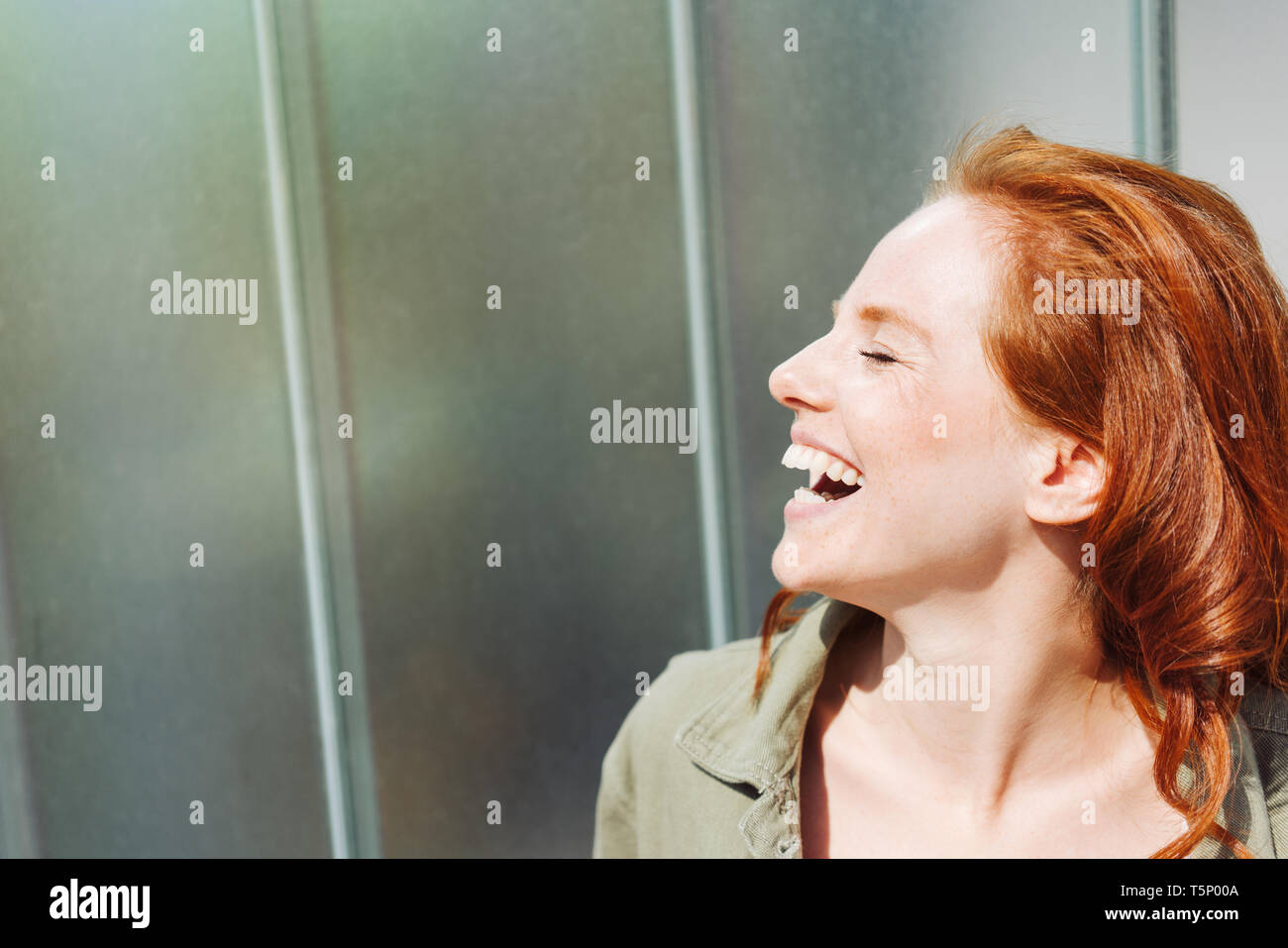 Happy young woman laughing merrily as she stands in front of a commercial building with her head thrown back and eyes closed - Stock Image