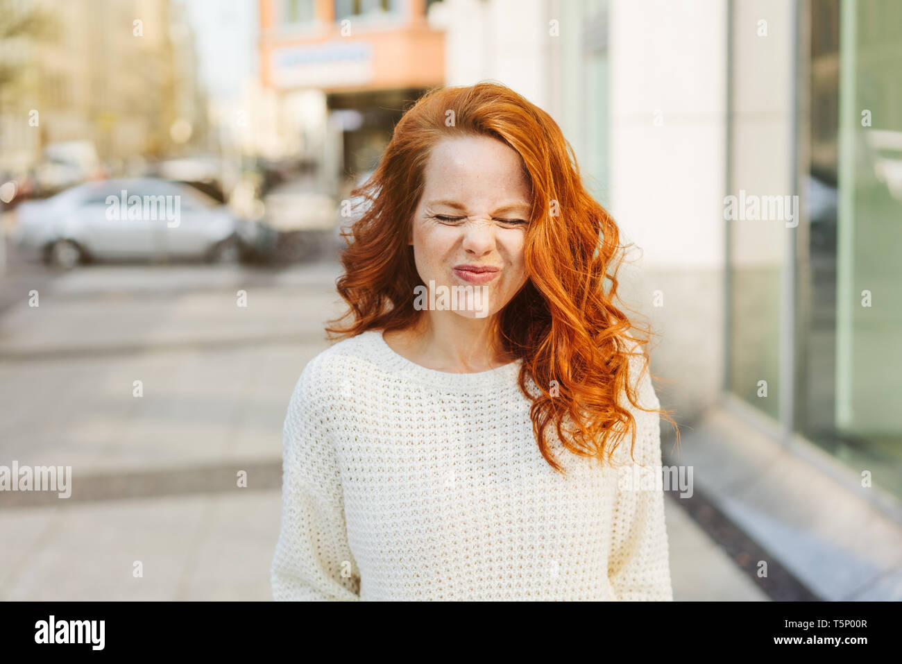 Pretty young woman screwing up her face grimacing in distaste as she stands on a pavement on a city street - Stock Image