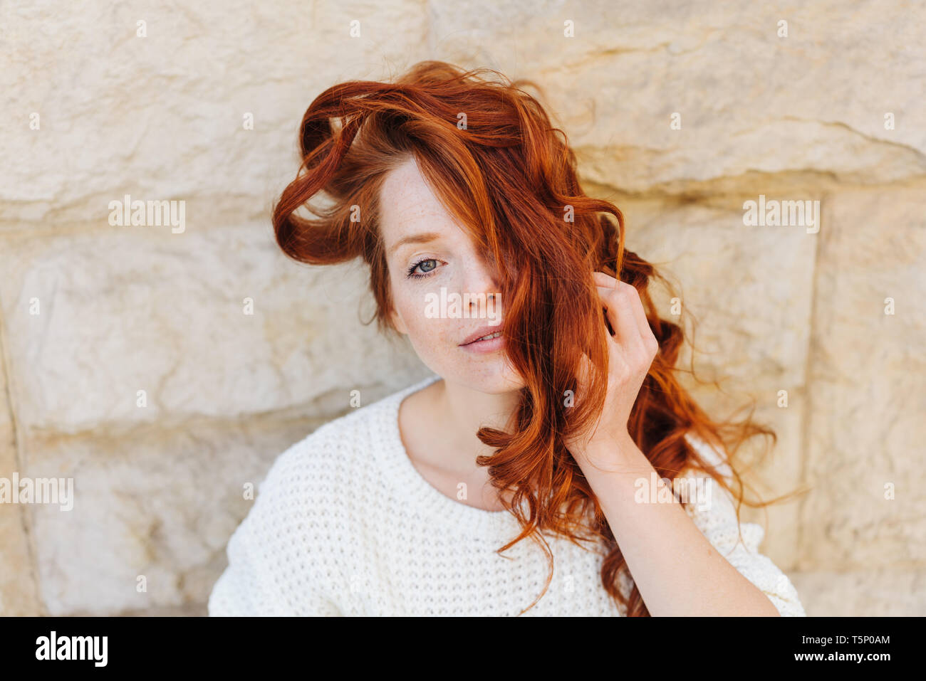 Thoughtful young woman with tousled red hair over her face standing in front of a rough stone wall peering quietly at the camera - Stock Image
