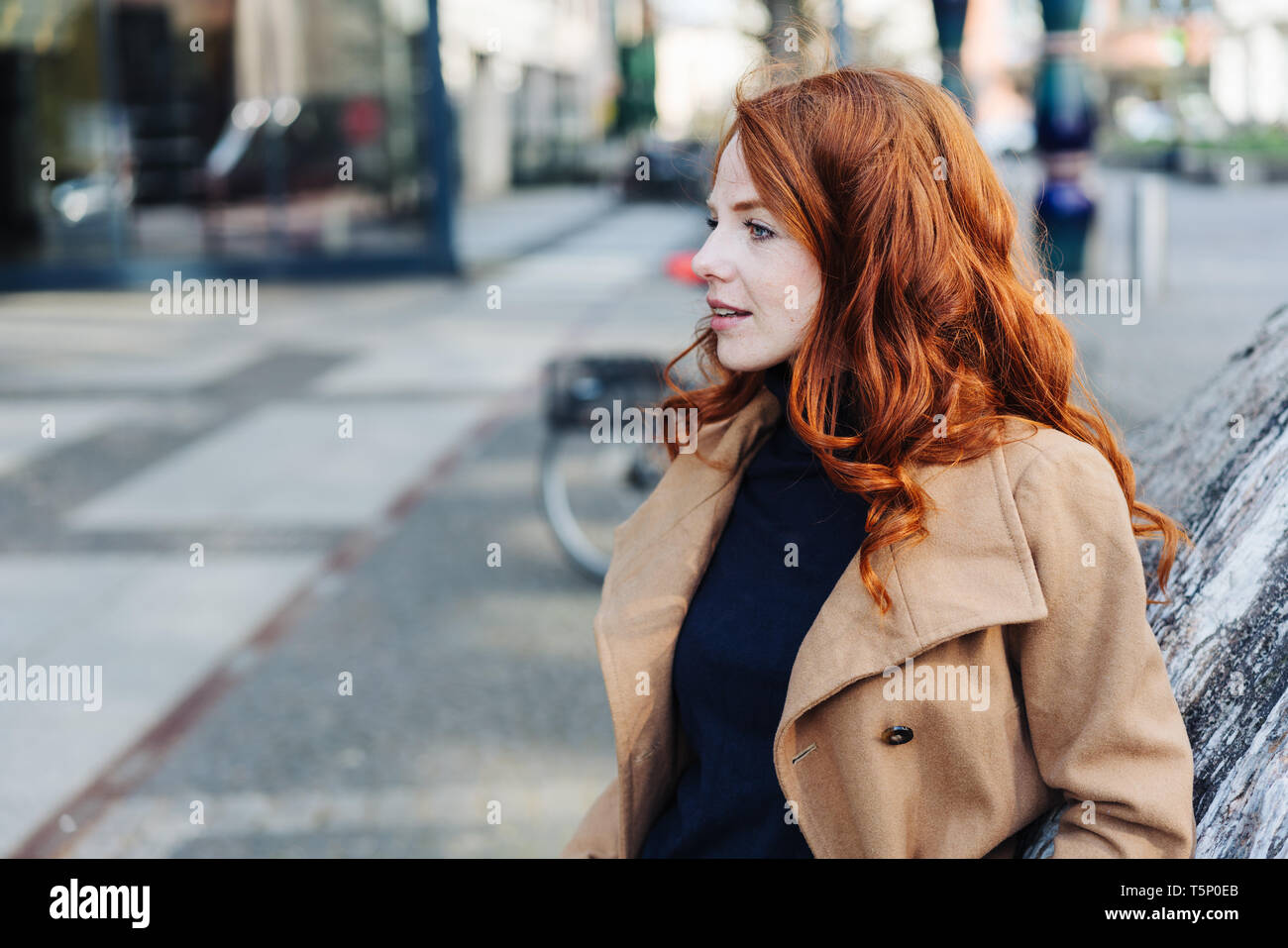 Thoughtful stylish young woman with tousled long red hair standing in a city street in a brown trench coat looking to the side with interest - Stock Image