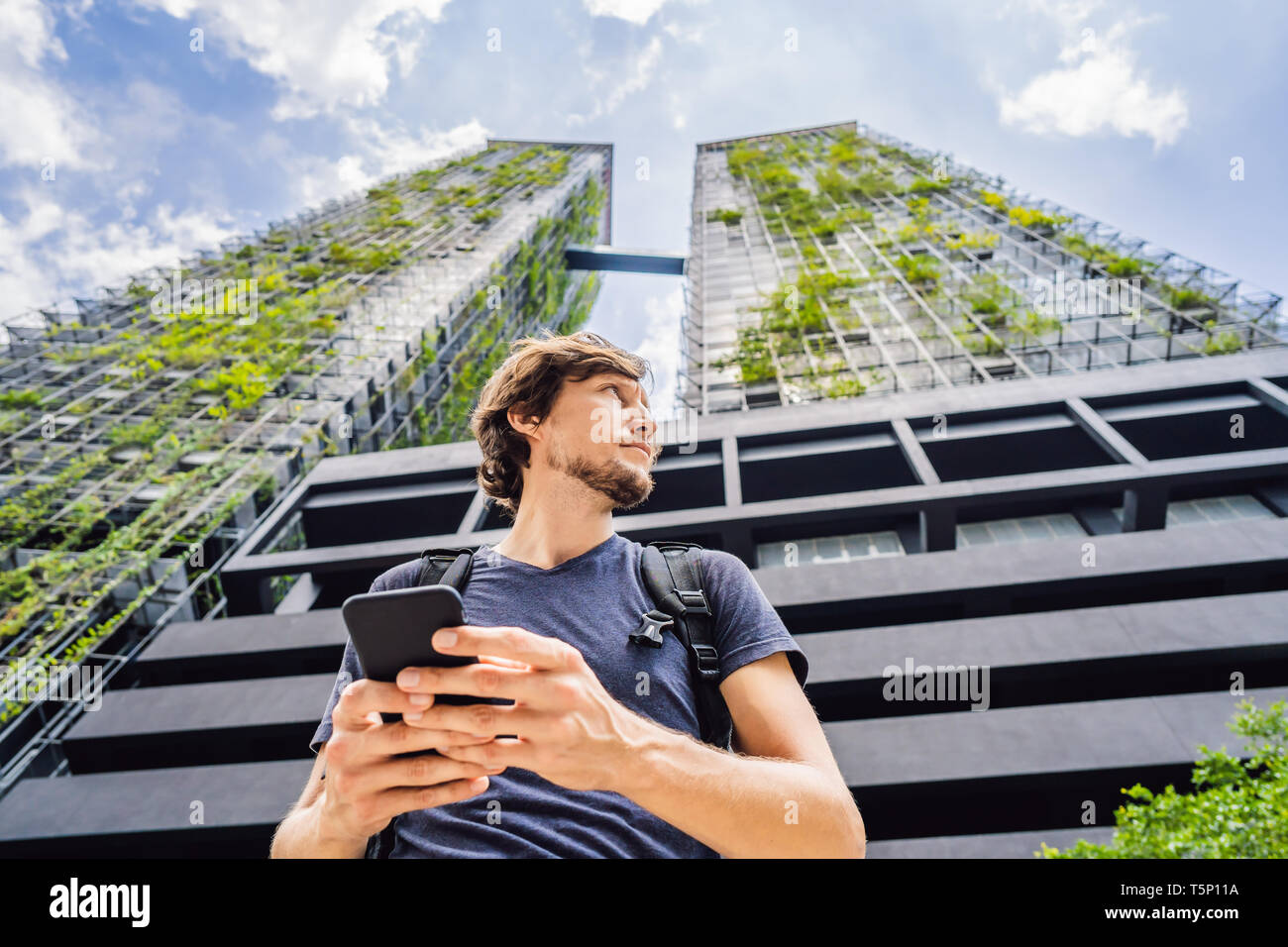man using map app on smartphone on the background of skyscrapers - Stock Image