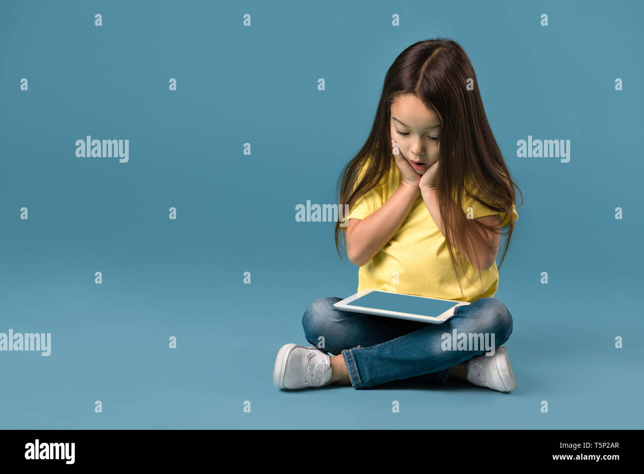 surprised cute little child girl holding blank tablet computer on blue background Stock Photo
