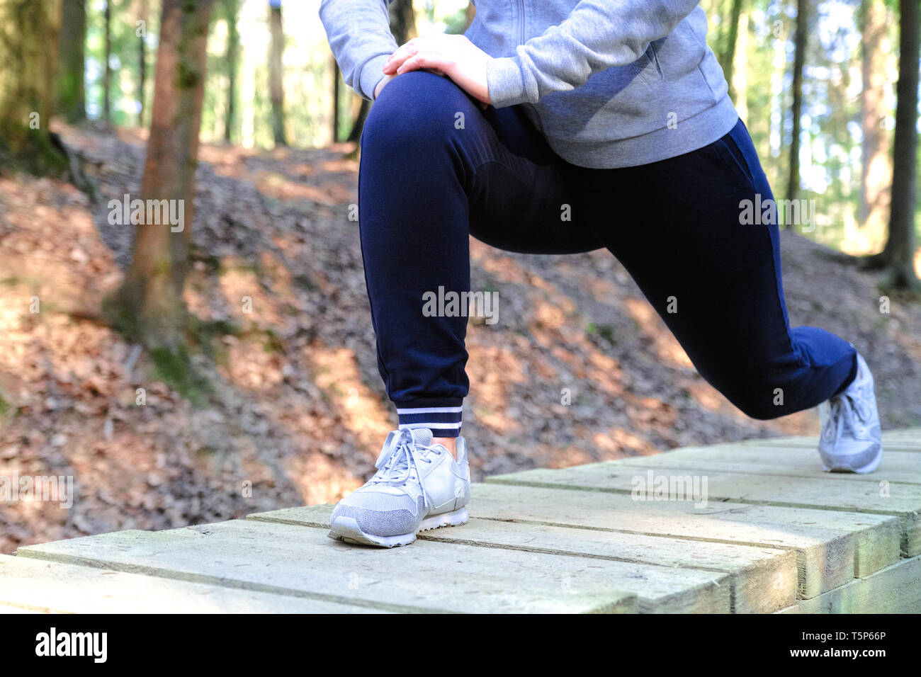 Sports injury. Woman with pain in knee while jogging Stock Photo