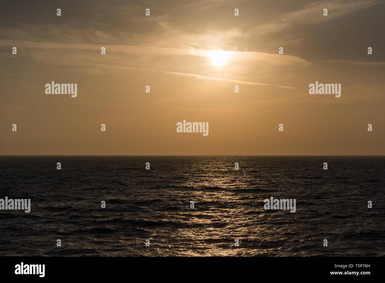 Orange sunset above sea from ship - Stock Image