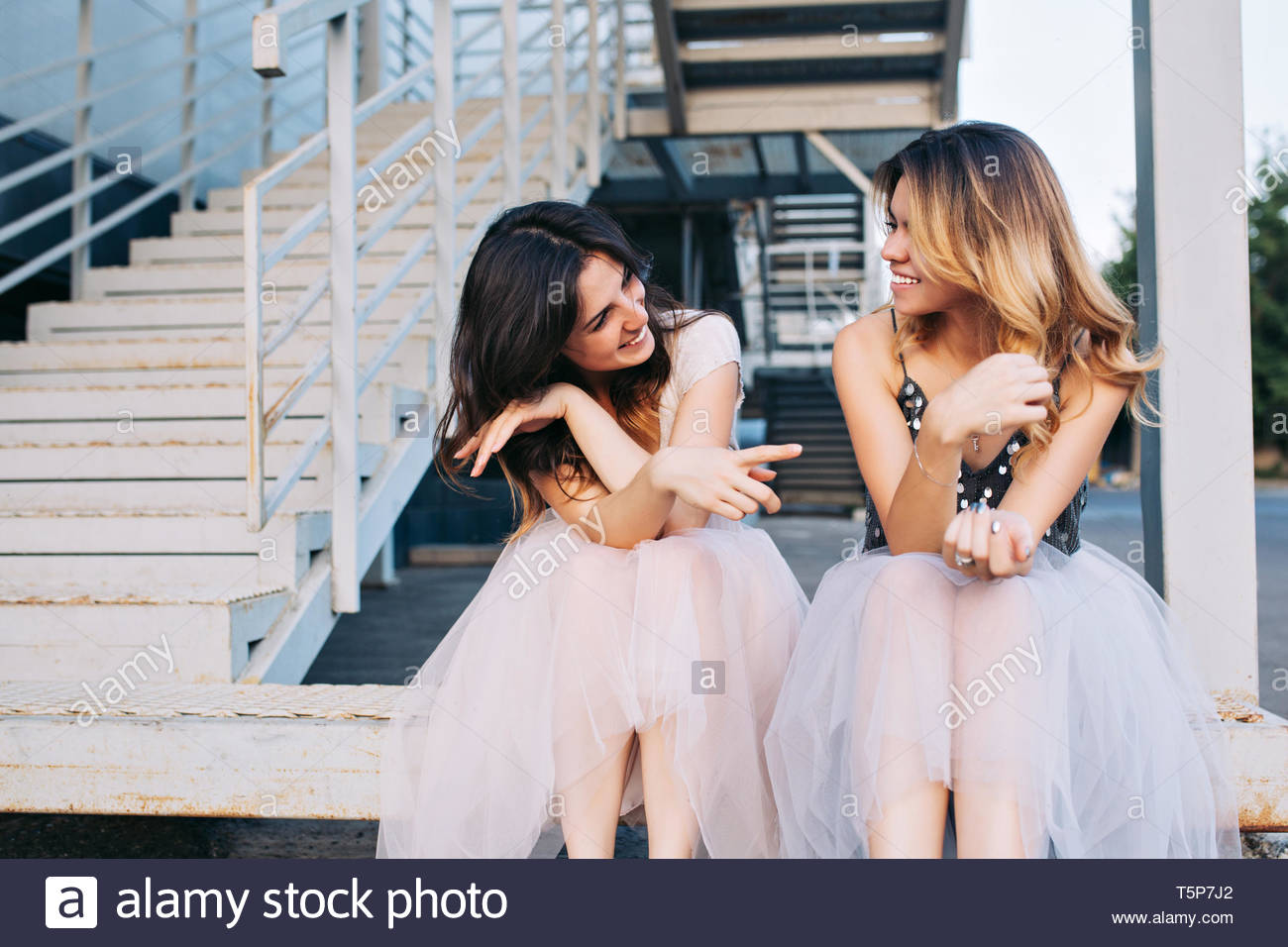 Brunette and blonde fashion attractive girls sitting on stairs in tulle skirts. They having fun and smiling to each other - Stock Image