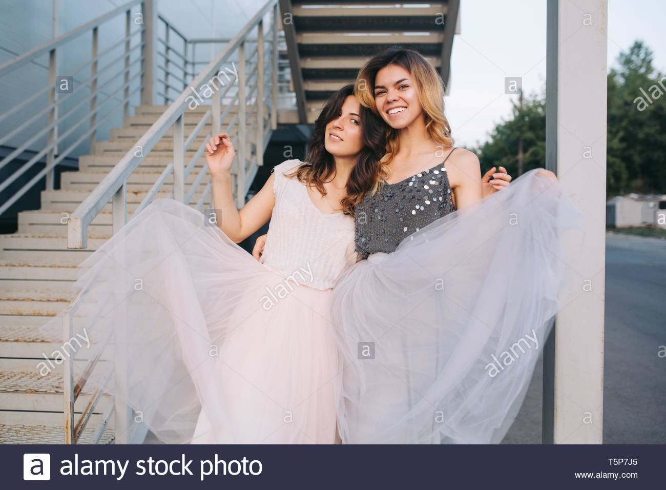 Beautiful models hugging outdoor near stairs. They wear flying tulle skirts, looking to camera - Stock Image