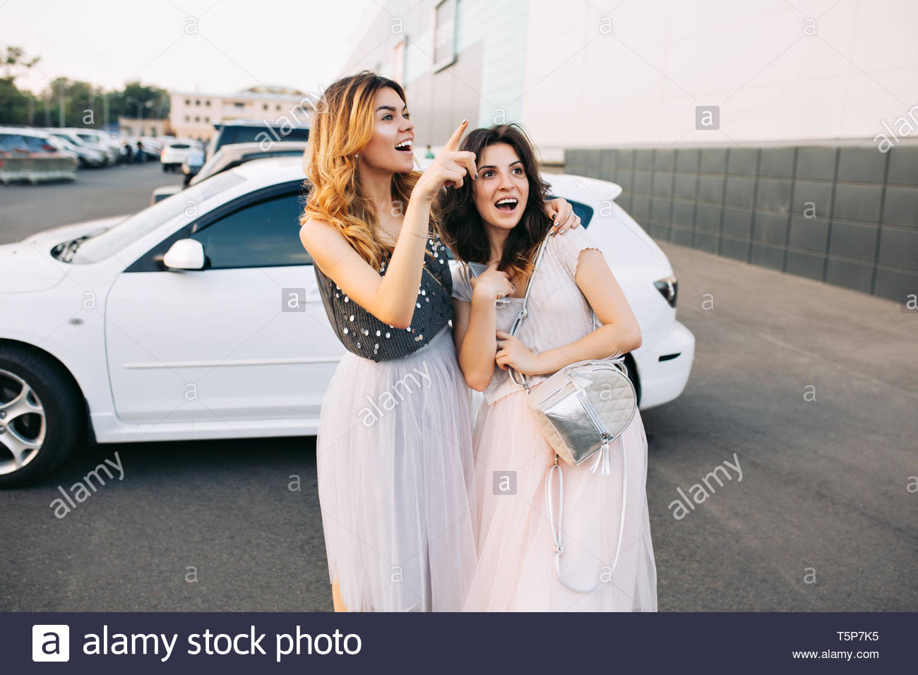 Two pretty girls in  tulle skirts having fun on parking. They looking surprised and excited far away - Stock Image