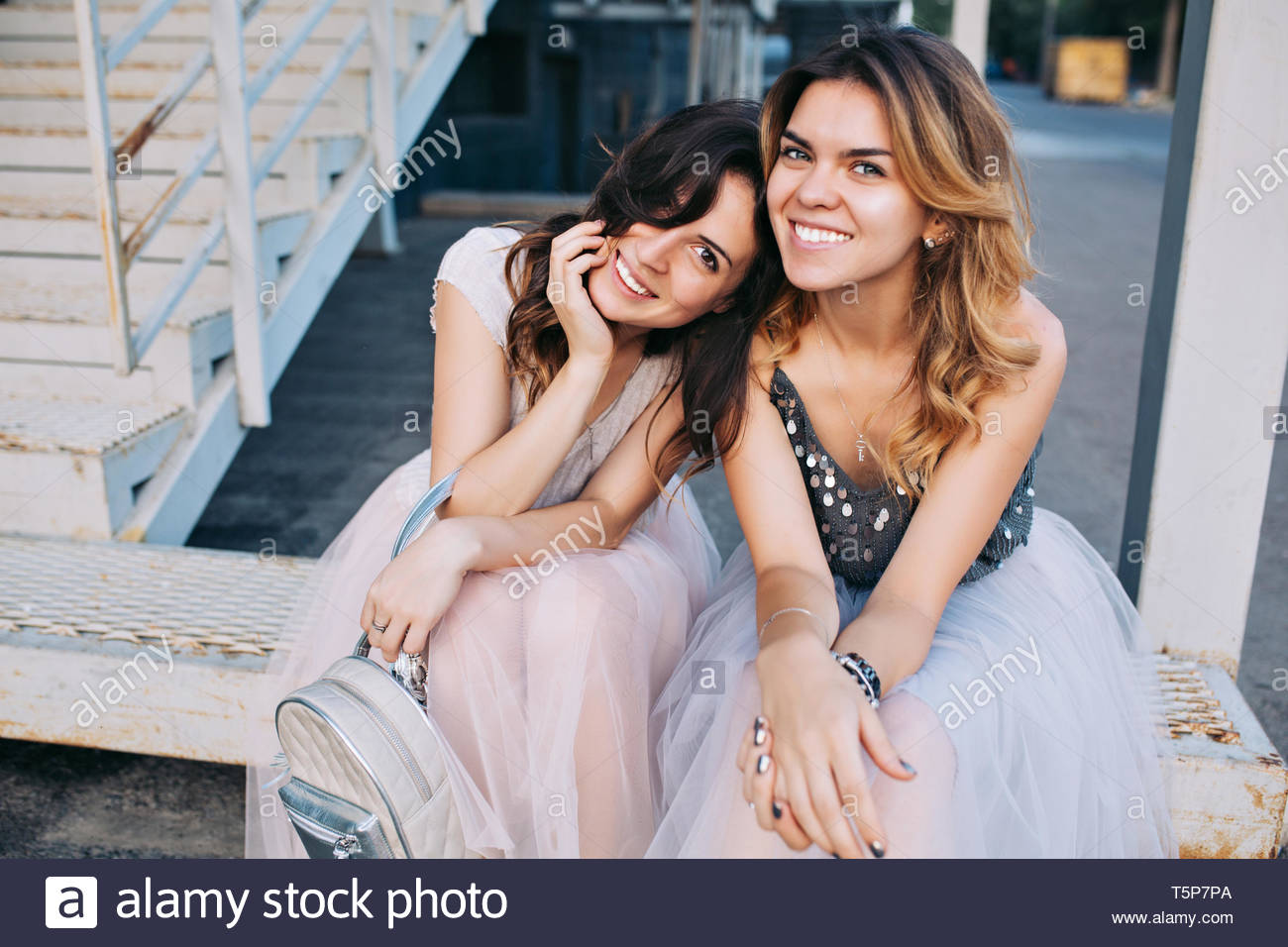 Portrait of two attractive girls in tulle skirts sitting outdoor on stairs. They smiling to camera - Stock Image