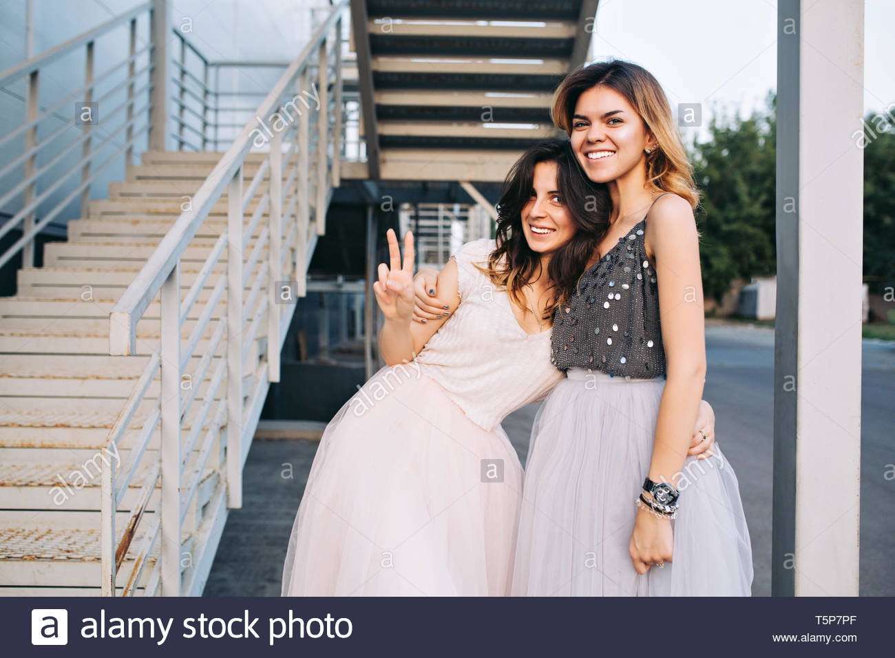 Two pretty girls in tulle skirts outside near grey stairs. They hugging and smiling to camera - Stock Image