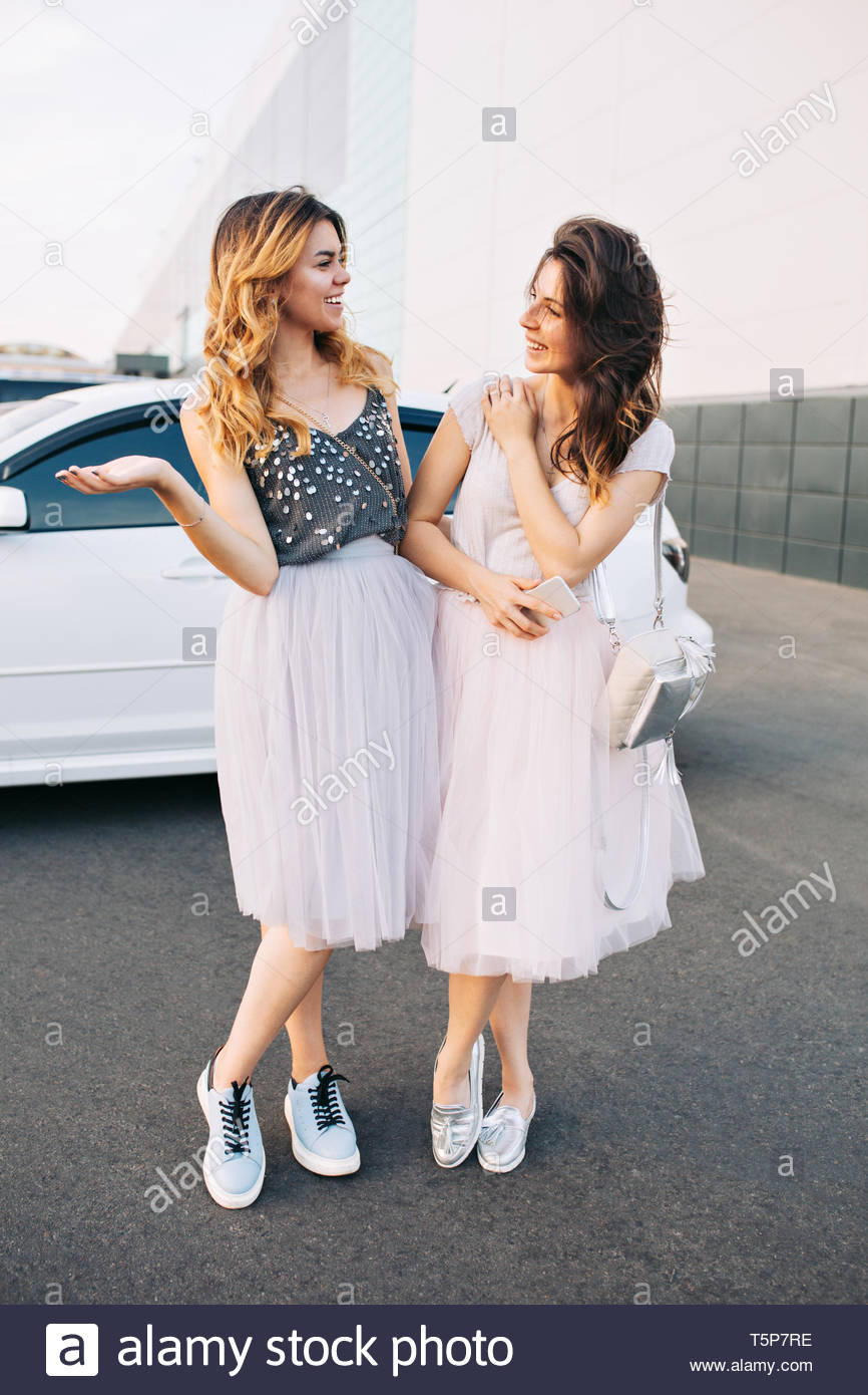 Two fashion attractive girls in light tulle skirts having fun on parking. They smiling to each other - Stock Image
