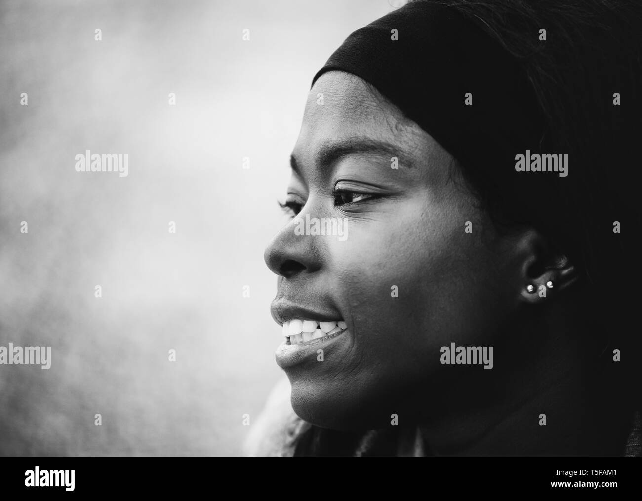 Black and white portrait of young beautiful African woman smiling in outdoor - Stock Image