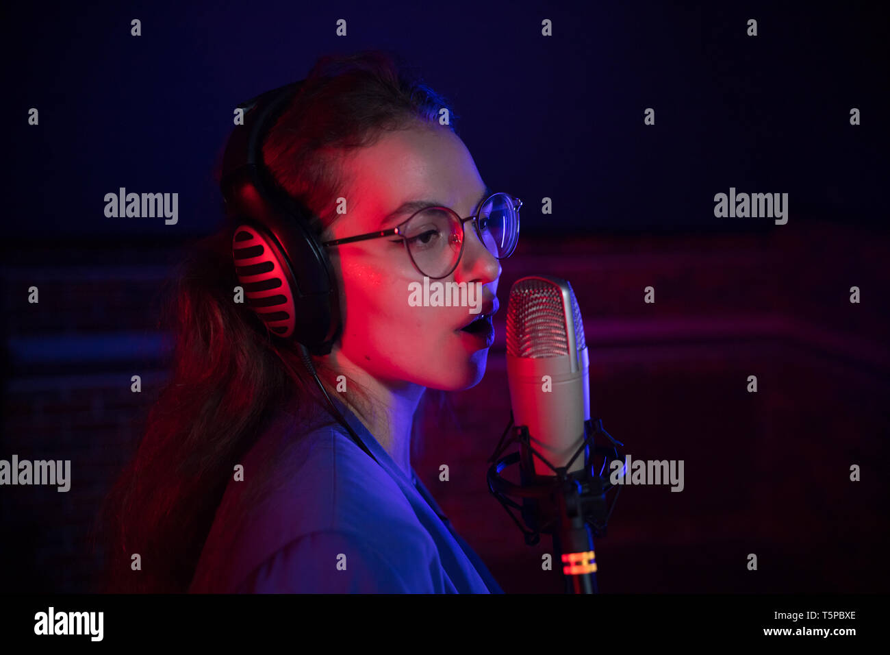 A young woman in glasses singing by the microphone in neon lighting Stock Photo