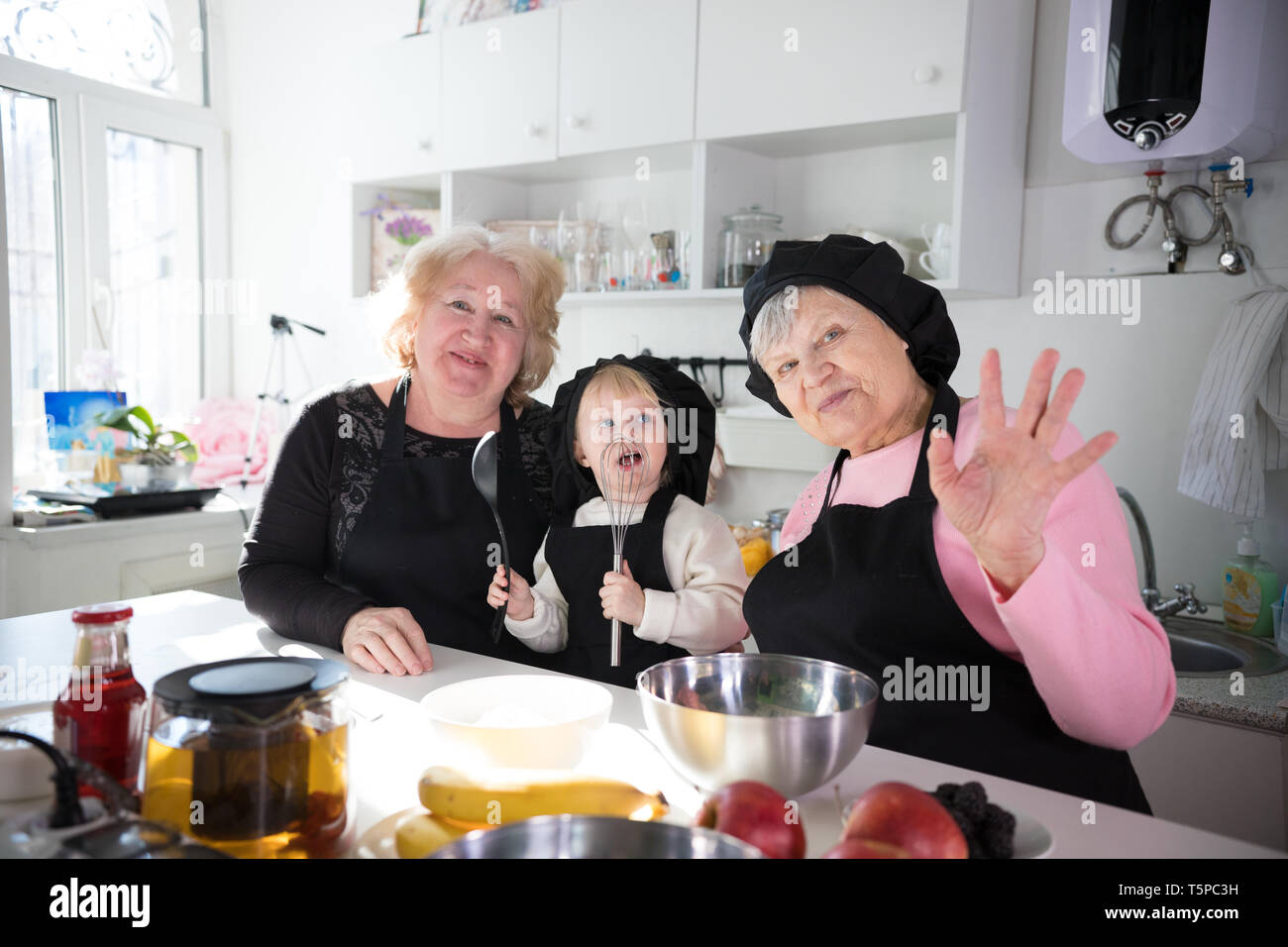 Family eating pancakes and drinking tea in the kitchen. Posing for the camera and waving hands Stock Photo