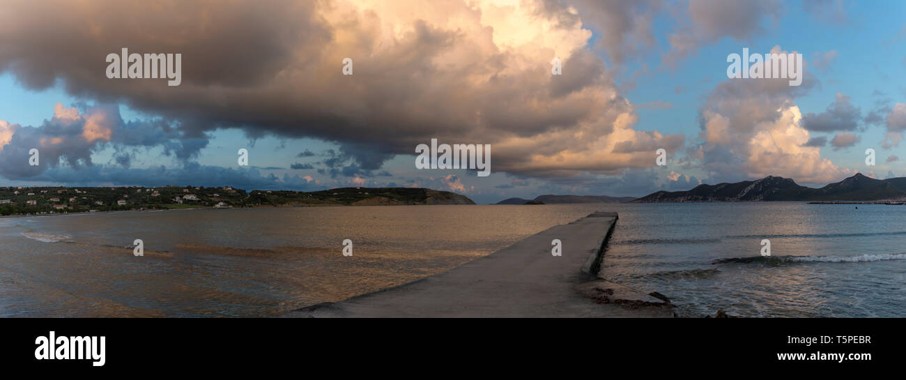 Dramatic sunset over sea water with gray clouds and sun lights, nature seascape - Stock Image