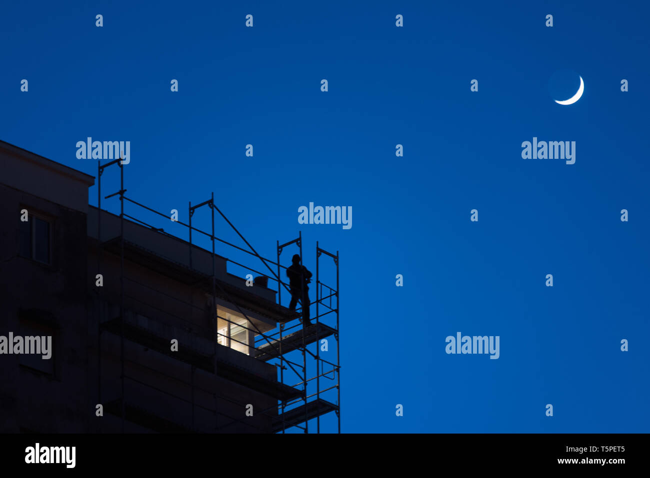 Silhouette of a man working high on a skyscraper scaffolding at twilight, dangerous work, security at work, blue sky with moon in the background - Stock Image