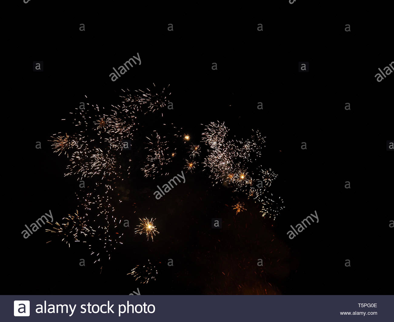 real simple fireworks at night sky over a burning fire - Stock Image