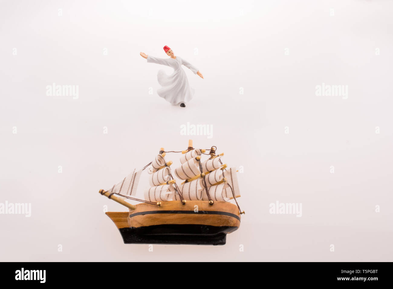 Sufi Dervish near a ship on a white background - Stock Image