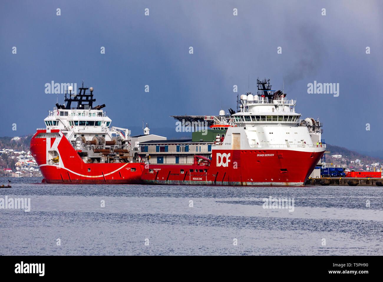 Offshore supply vessels KL Saltfjord and Skandi Bergen, in the port of Bergen, Norway. Skandi Bergen in the process of berthing at Skoltegrunnskaien t - Stock Image