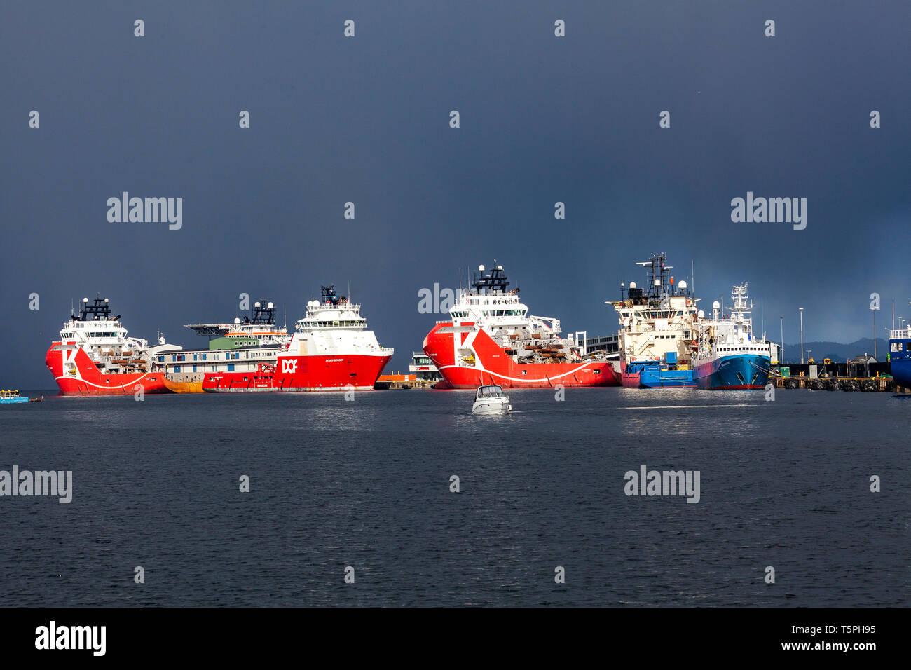 Offshore supply vessels KL Sandefjord, Skandi Bergen, KL Saltfjord and Deep Vision, in the port of Bergen, Norway. Skoltegrunnskaien terminal. A heavy - Stock Image