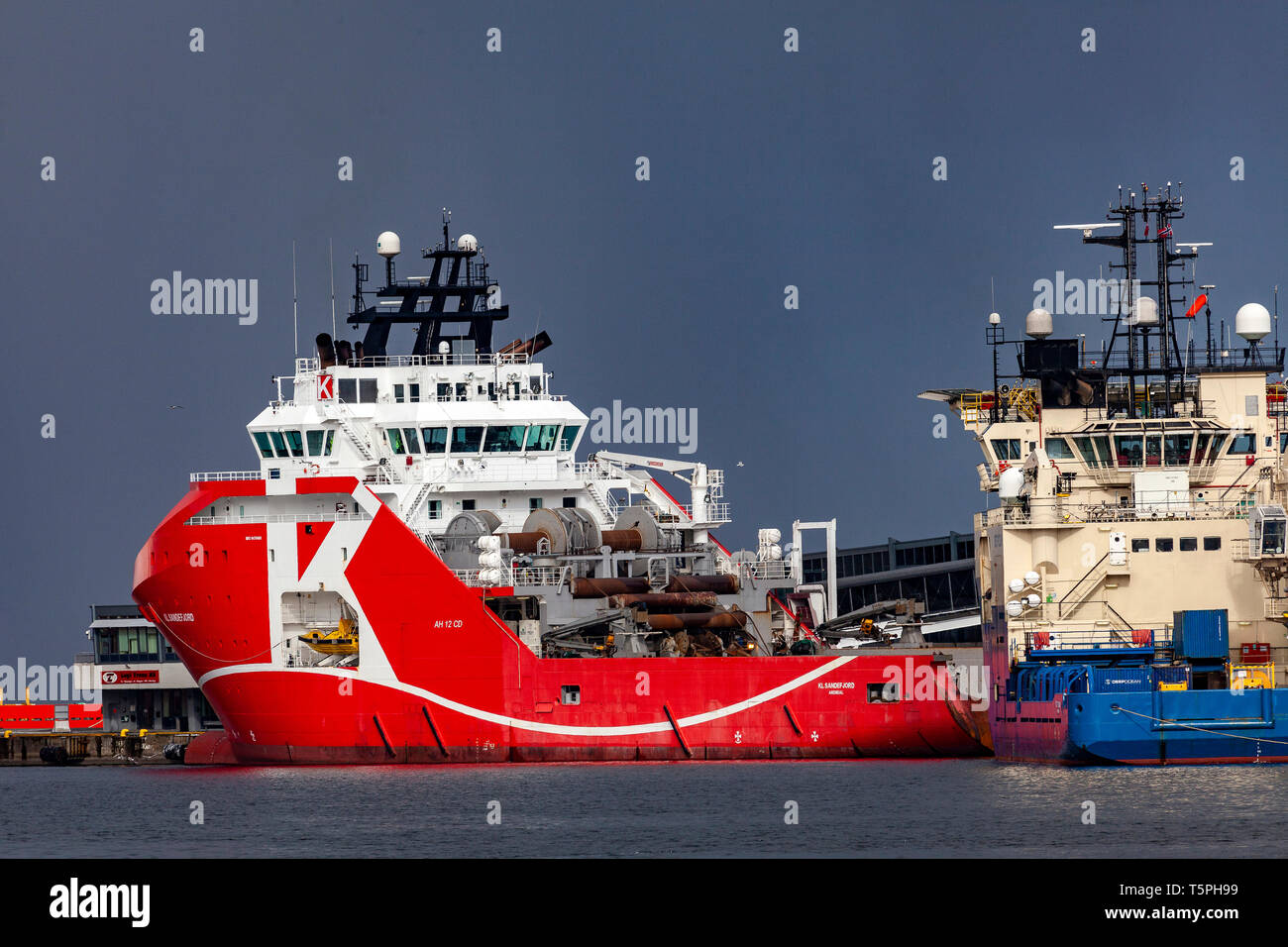Offshore AHTS supply vessel KL Sandefjord, at Skoltegrunnskaien terminal in the port of Bergen, Norway. A heavy snowstorm approaching.  To the right,  - Stock Image