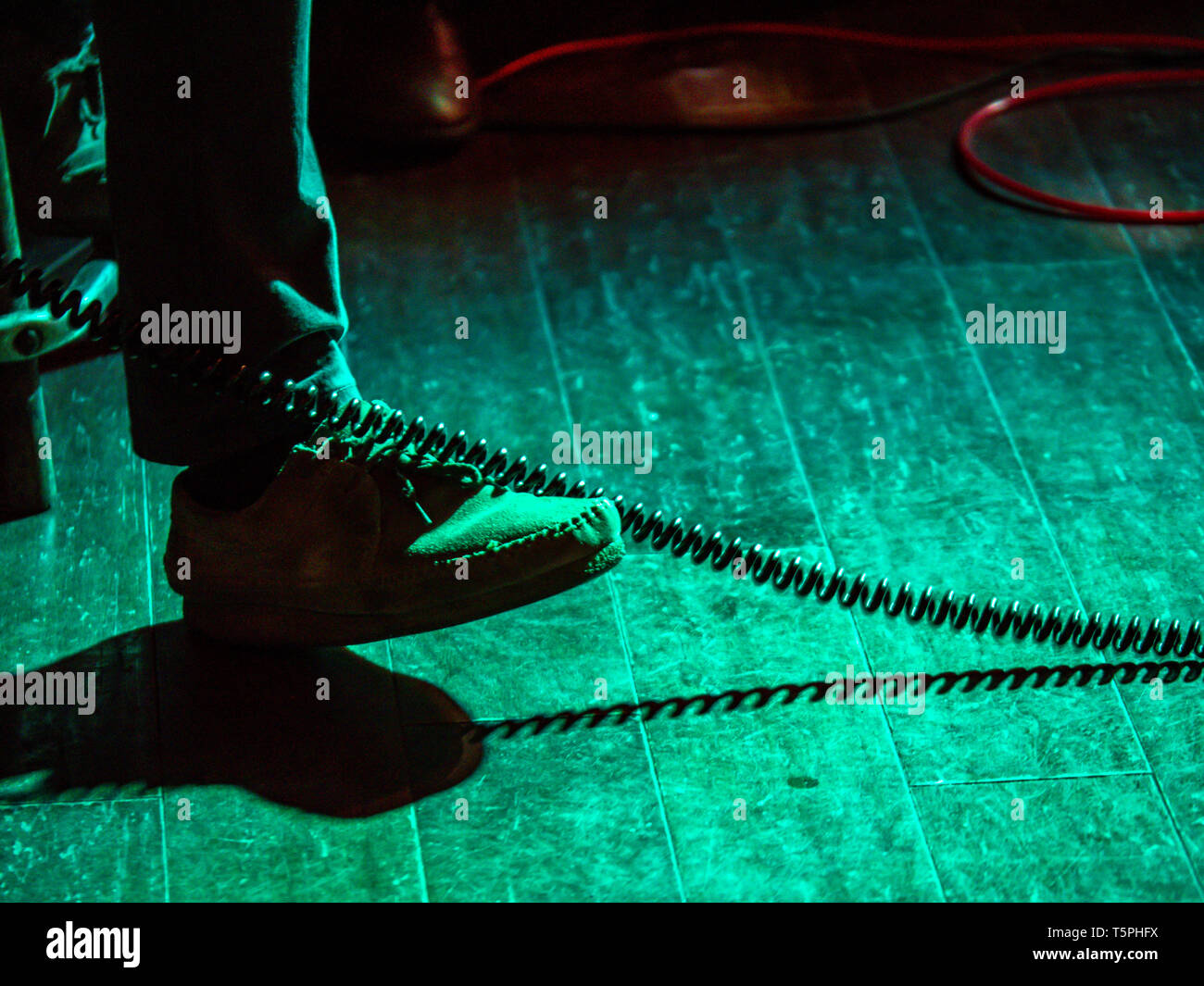 Foot tapping in rhythm of musical performance in a dimly lit stage - Stock Image