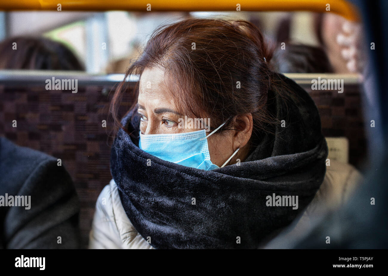 Older Asian woman wearing black fur scarf and surgical pollution mask sitting on a bus train subway - Stock Image