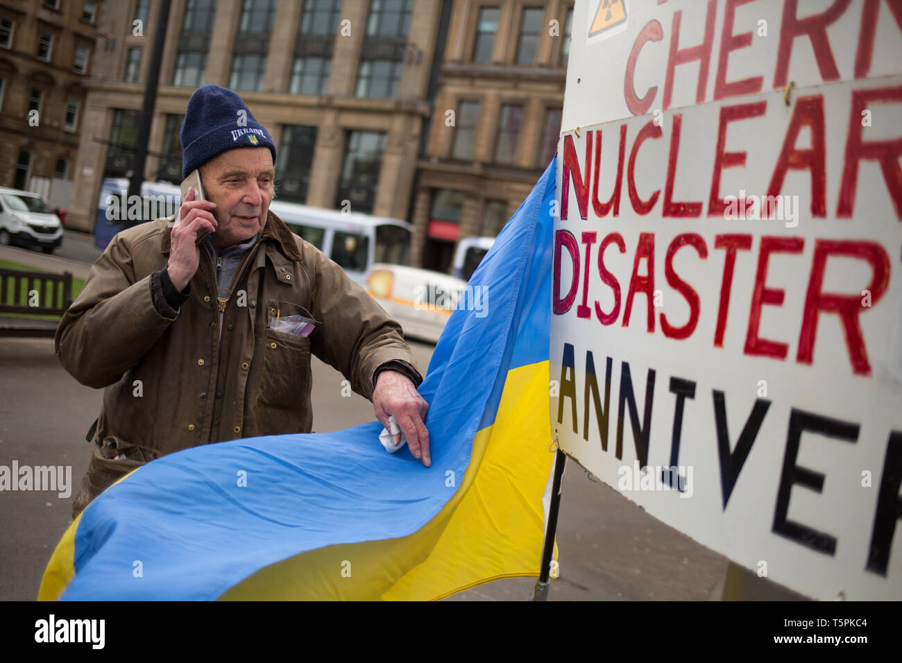 Glasgow, Scotland, 26th April 2019. 78-years old Jim Gillies stands in George Square with his placard remembering the 1986 Chernobyl nuclear disaster in the Ukraine. Today marks the 33rd anniversary of the disaster and Jim Gillies has marked the disaster day, by standing with his placard in the Square ever year since, as well as donating more than £20,000 GBP to a hospital in Ukraine, a country he has now visited approximately 20 times. Credit: jeremy sutton-hibbert/Alamy Live News - Stock Image