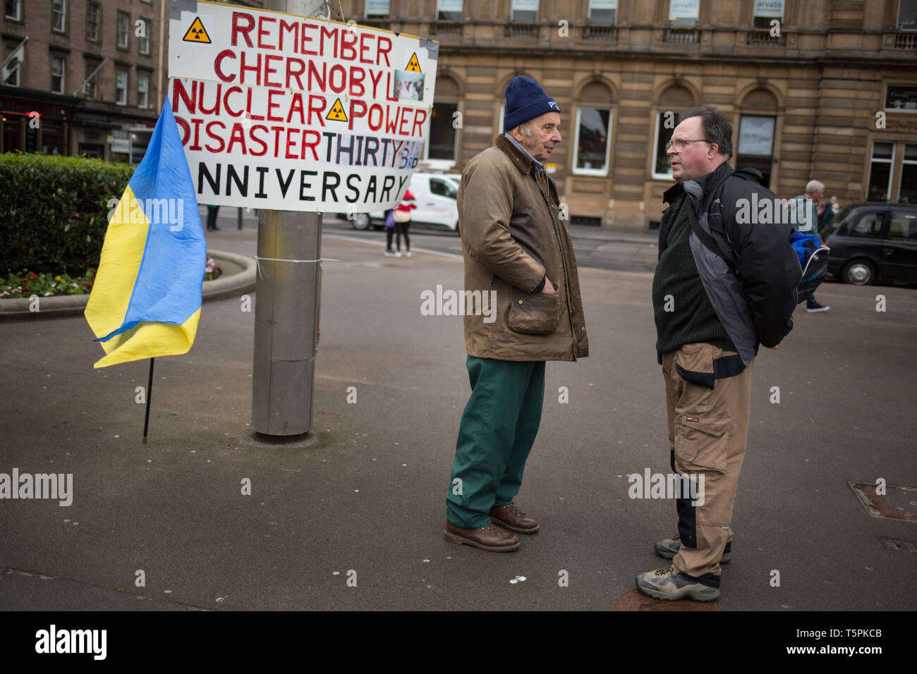 Glasgow, Scotland, 26th April 2019. 78-years old Jim Gillies (on left) stands in George Square with his placard remembering the 1986 Chernobyl nuclear disaster in the Ukraine. Today marks the 33rd anniversary of the disaster and Jim Gillies has marked the disaster day, by standing with his placard in the Square ever year since, as well as donating more than £20,000 GBP to a hospital in Ukraine, a country he has now visited approximately 20 times. Credit: jeremy sutton-hibbert/Alamy Live News - Stock Image