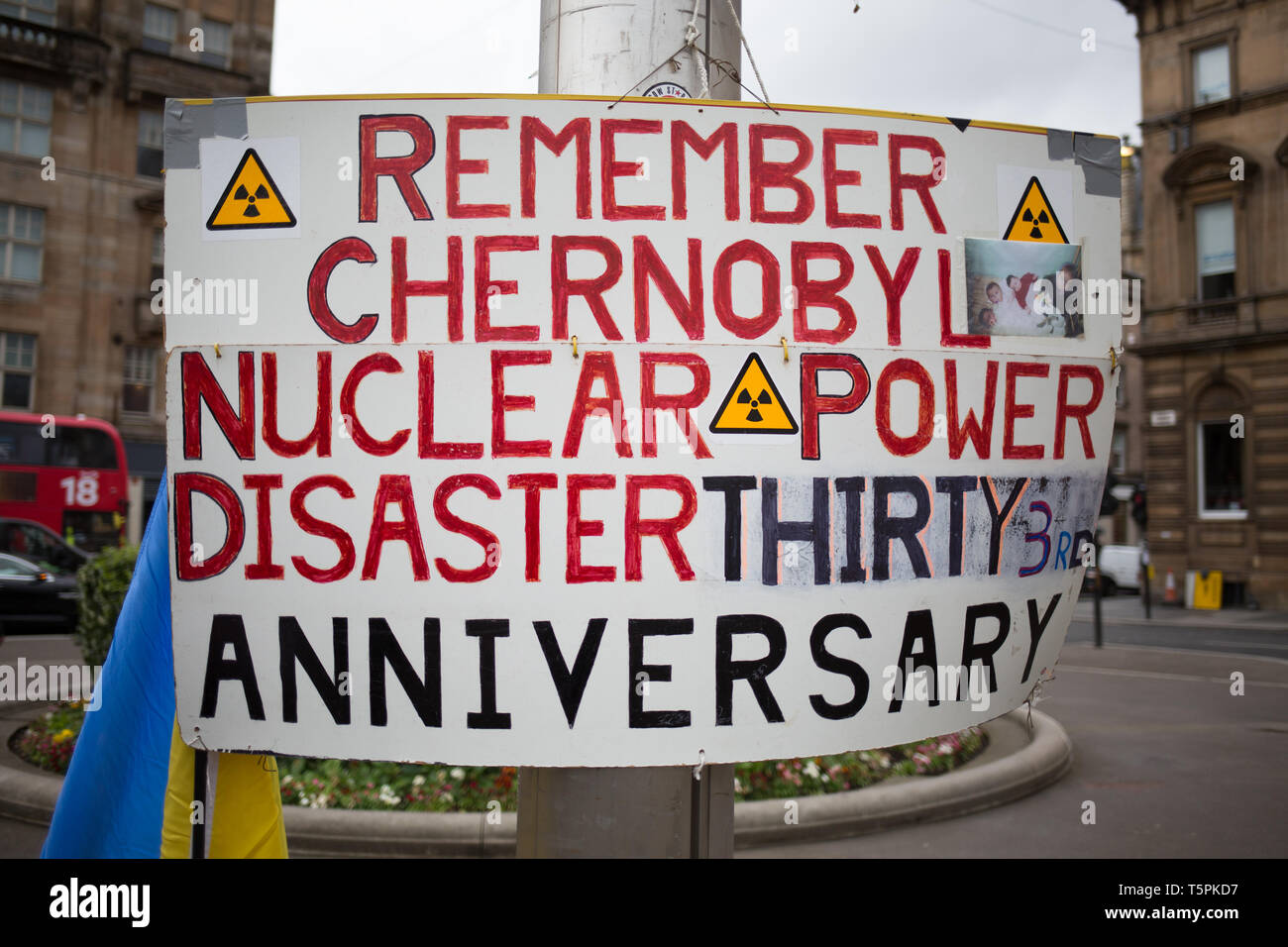 Glasgow, Scotland, 26th April 2019. 78-years old Jim Gillies stands in George Square with his placard remembering the 1986 Chernobyl nuclear disaster in the Ukraine. Today marks the 33rd anniversary of the disaster and Jim Gillies has marked the disaster day, by standing with his placard in the Square ever year since, as well as donating more than £20,000 GBP to a hospital in Ukraine, a country he has now visited approximately 20 times. Credit: jeremy sutton-hibbert/Alamy Live News Stock Photo