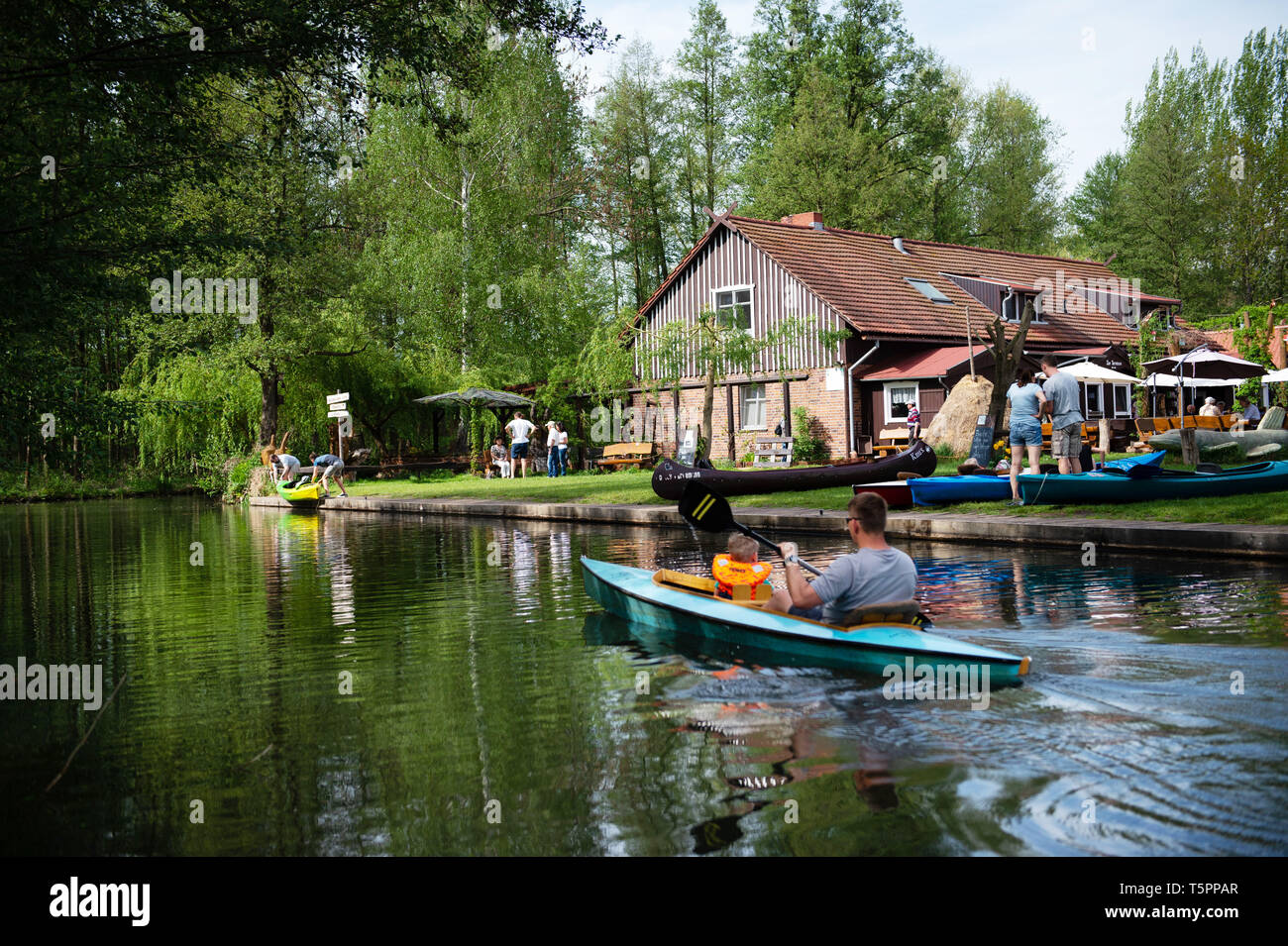 Leipe, Germany. 26th Apr, 2019. Tourists pass the Spreewaldhof inn in a canoe on the main river Spree. (to dpa 'Lusatia: Successful season opener with many tourists') Credit: Lisa Ducret/dpa/Alamy Live News - Stock Image