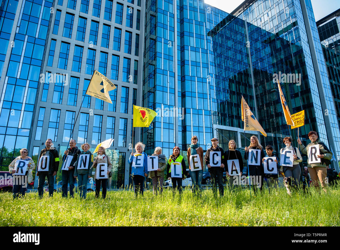 """April 26, 2019 - Brussels, North Brabant, Belgium - A group of activists are seen holding placards with the word cancer in front of the Engie HQ during the protest..On the day that commemorates the 33rd anniversary of the Chernobyl nuclear disaster, a protest was organized by the """"Fin du nucléaire"""" and Réveil Anti-Nucléaire"""" associations, as well as director Bouli Lanners. They want the five most dangerous Belgian reactors to be shut down. (Credit Image: © Ana Fernandez/SOPA Images via ZUMA Wire) - Stock Image"""