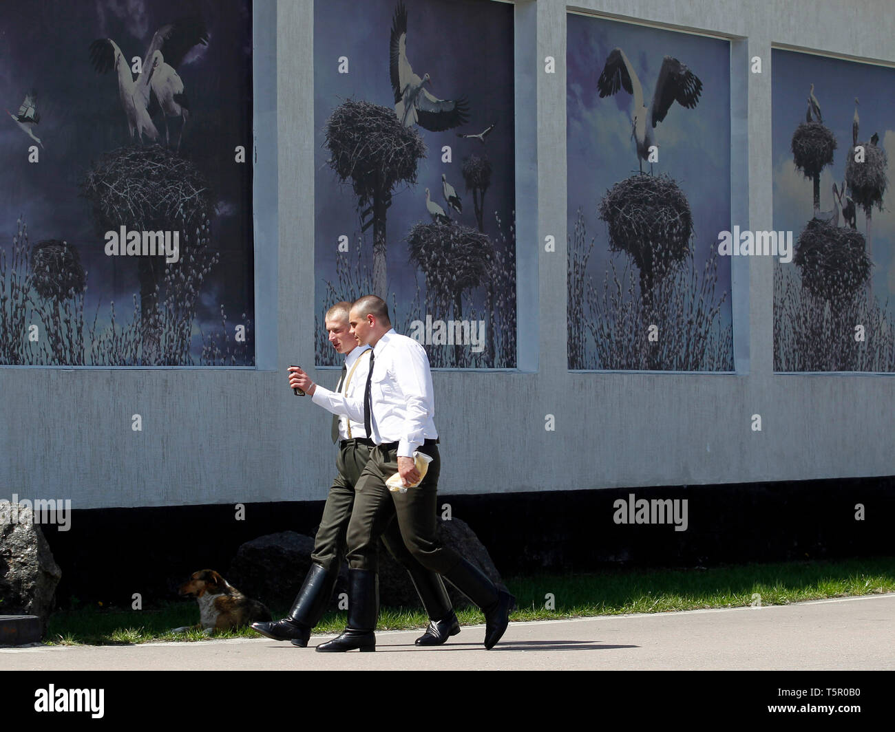 Two men are seen walking next to images of a local museum dedicated to the Chernobyl disaster during the anniversary. Ukrainians mark the 33rd anniversary of Chernobyl catastrophe. The explosion of the fourth block of the Chernobyl nuclear plant on 26 April 1986 is still regarded as the biggest accident in the history of nuclear power generation. - Stock Image