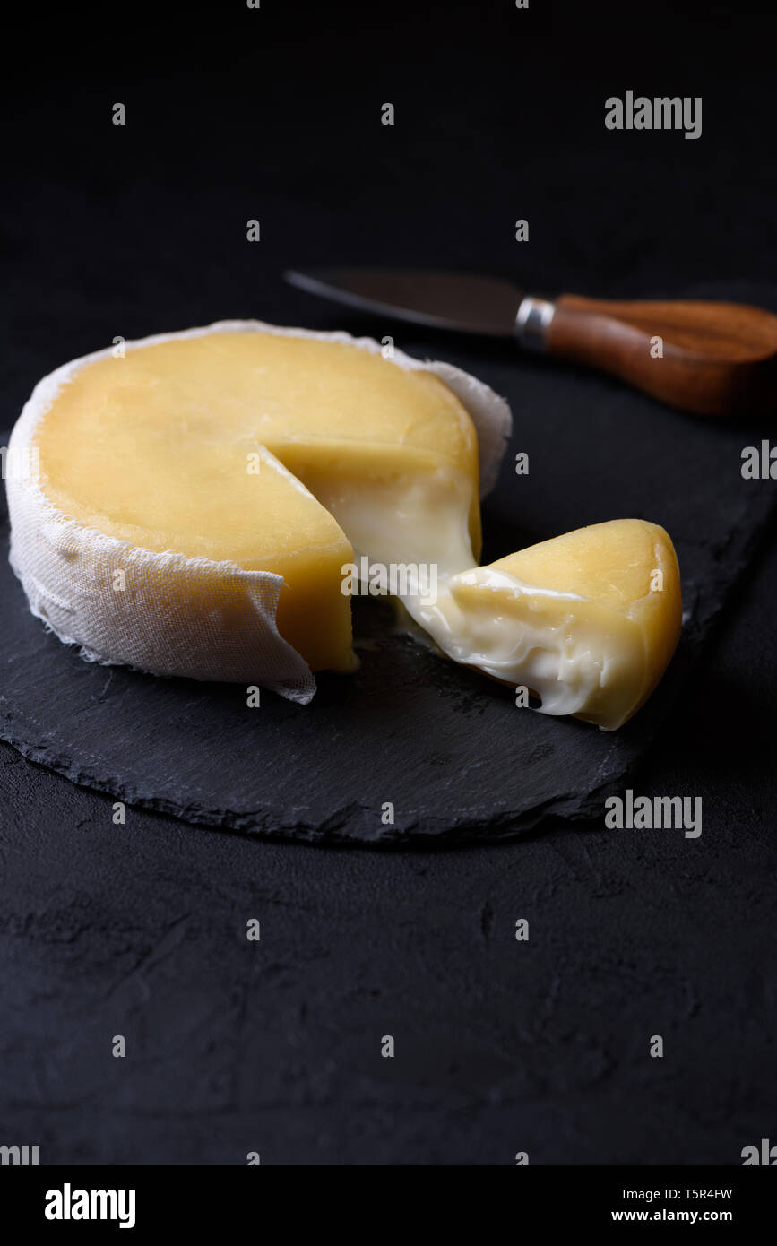Butter soft creamy sheep cheese from Seia region Portugal on black slate board, with one piece cut and cheese melting - Stock Image