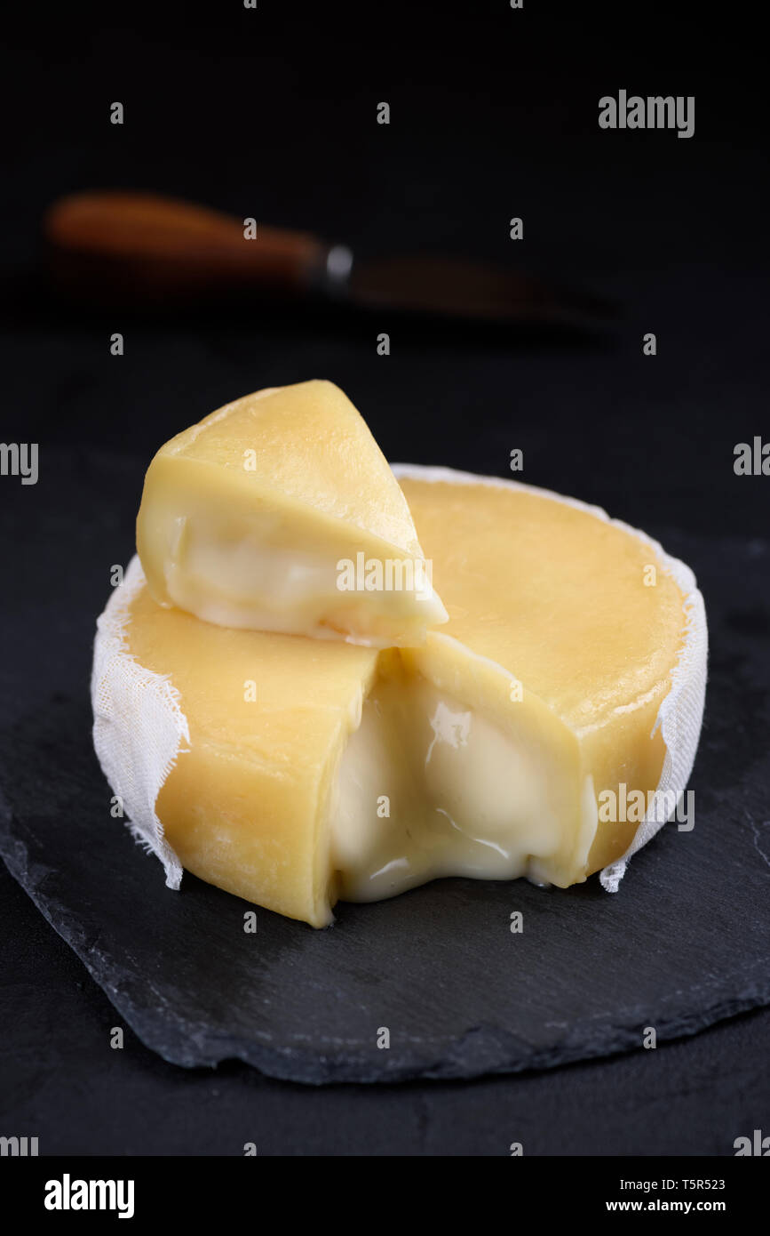 Soft round cheese on slate background with one piece cut - Stock Image