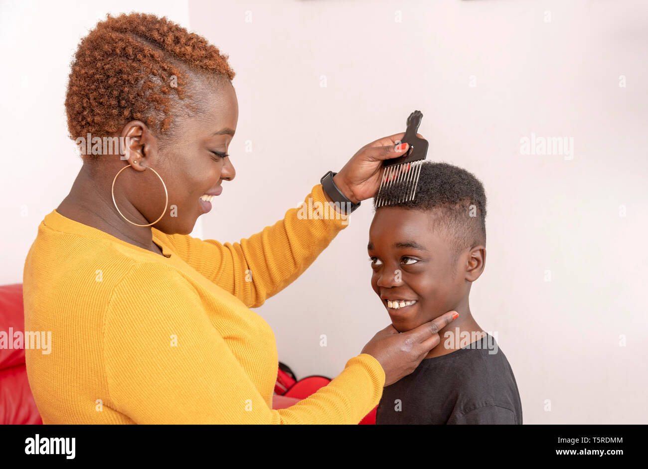 Andover, Hampshire, England, UK. April 2019. Nine year old boy with curly hair with his mother using a wide tooth afro comb for his hair. Stock Photo