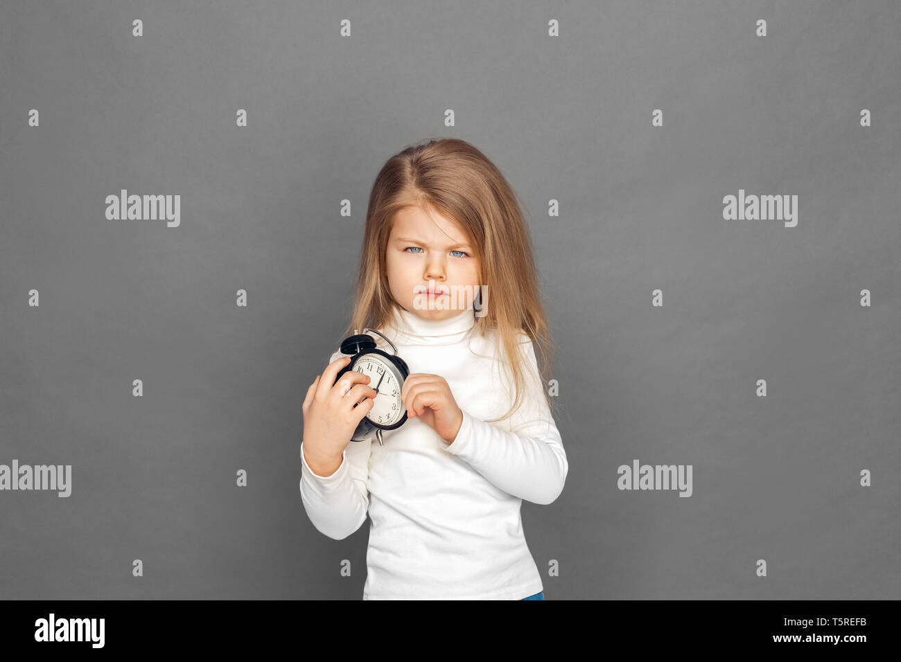Little girl standing isolated on grey background holding alarm clock looking camera grimacing unhappy - Stock Image