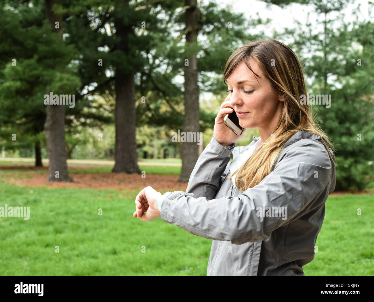 Young woman on cell, mobile phone looking at watch in city park on overcast day, smiling, with green grass, trees background - Stock Image