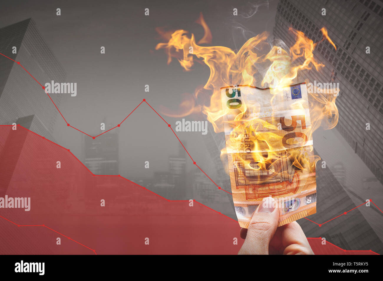 Loosing money concept – burning 50€ bill in front of a declining graph - Stock Image